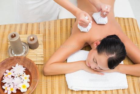 Peaceful brunette enjoying a herbal compress massageの素材 [FYI00002440]