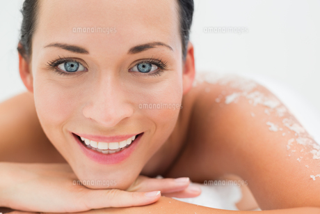 Peaceful brunette lying with salt scrub on back smiling at cameraの写真素材 [FYI00002442]