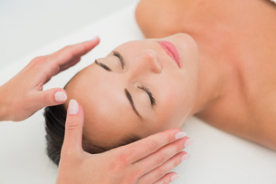 Peaceful brunette getting reiki therapyの写真素材 [FYI00002448]