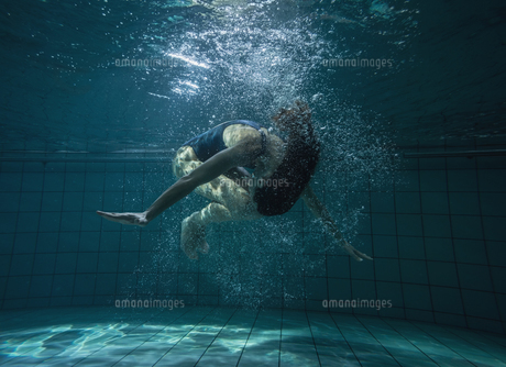 Athletic swimmer doing a somersault underwaterの写真素材 [FYI00002451]