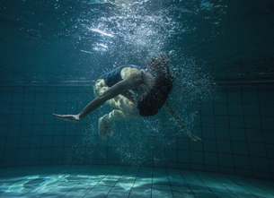 Athletic swimmer doing a somersault underwaterの素材 [FYI00002451]