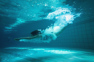 Athletic swimmer smiling at camera underwaterの素材 [FYI00002452]