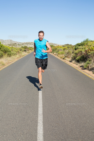 Fit man jogging on the open roadの写真素材 [FYI00002460]