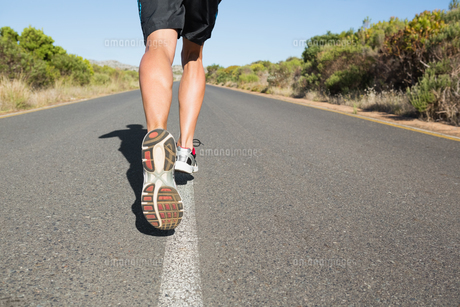 Fit man jogging on the open roadの写真素材 [FYI00002461]