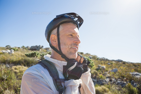 Fit cyclist adjusting helmet strap on country terrainの写真素材 [FYI00002468]