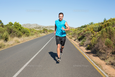 Fit man jogging on the open roadの写真素材 [FYI00002471]