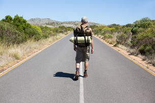 Handsome hiker walking on road and smiling at cameraの写真素材 [FYI00002475]