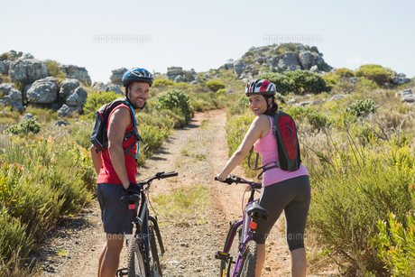 Active couple cycling in the countryside smiling at cameraの写真素材 [FYI00002480]