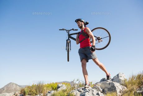 Fit cyclist carrying his bike on rocky terrainの素材 [FYI00002483]