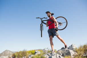 Fit cyclist carrying his bike on rocky terrainの写真素材 [FYI00002483]