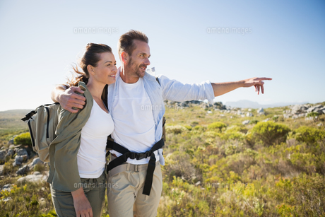 Hiking couple pointing and smiling on country terrainの写真素材 [FYI00002485]