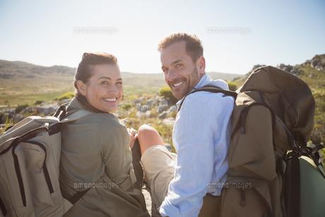 Hiking couple sitting on mountain terrain smiling at cameraの写真素材 [FYI00002487]