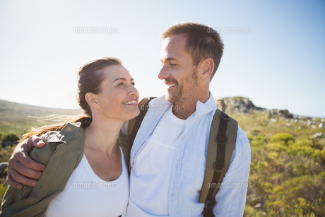 Hiking couple embracing and smiling on country terrainの写真素材 [FYI00002489]