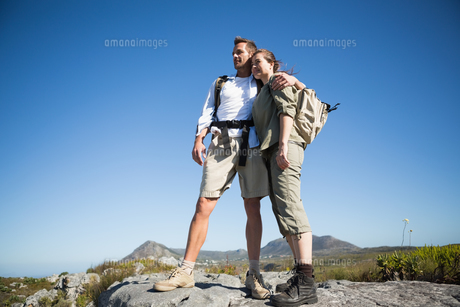 Hiking couple looking out over mountain terrainの写真素材 [FYI00002490]