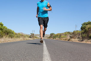 Athletic man jogging on open roadの写真素材 [FYI00002494]