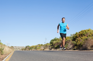 Athletic man jogging on the open roadの写真素材 [FYI00002495]