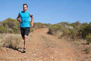 Athletic man jogging on country trailの写真素材 [FYI00002497]