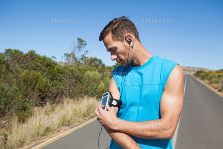Athletic man adjusting his music player on a runの素材 [FYI00002498]