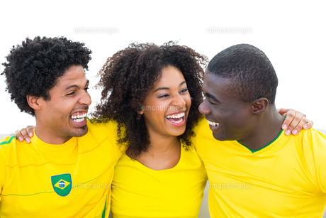 Happy brazilian football fans in yellow smiling at each otherの写真素材 [FYI00002503]