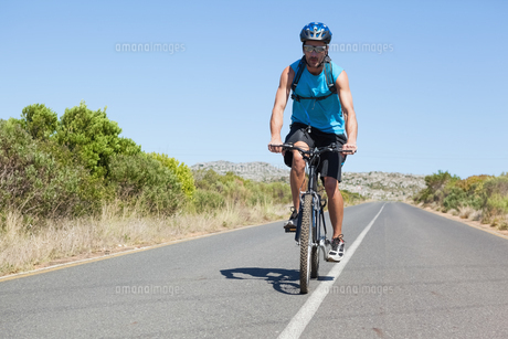 Athletic man cycling on open roadの写真素材 [FYI00002504]