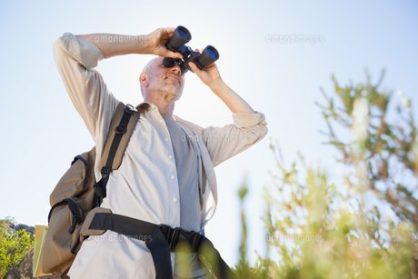 Hiker standing on country trail looking through binocularsの素材 [FYI00002505]