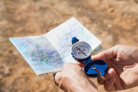 Hiker holding his compass and map in the countrysideの素材 [FYI00002510]