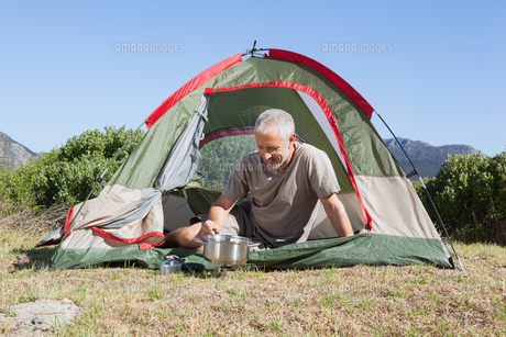 Happy camper cooking on camping stove outside his tentの写真素材 [FYI00002512]