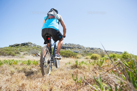 Fit cyclist riding in the countryside uphillの写真素材 [FYI00002514]