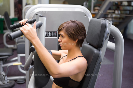 Happy brunette using weights machine for armsの写真素材 [FYI00002523]
