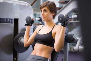 Smiling brunette using weights machine for armsの素材 [FYI00002527]