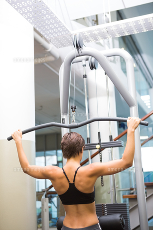 Fit brunette using weights machine for armsの写真素材 [FYI00002530]
