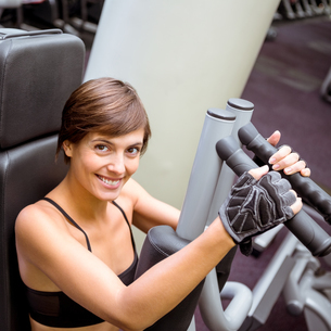 Focused brunette using weights machine for armsの写真素材 [FYI00002531]