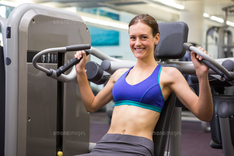 Fit smiling brunette using weights machine for armsの写真素材 [FYI00002532]