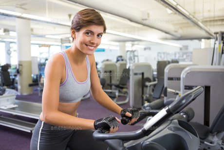 Fit brunette working out on the exercise bikeの写真素材 [FYI00002535]
