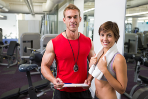 Handsome personal trainer with his client smiling at cameraの写真素材 [FYI00002542]