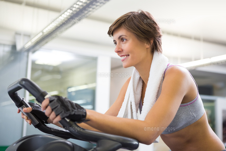 Fit smiling woman working out on the exercise bikeの写真素材 [FYI00002543]
