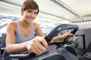Smiling brunette working out on the cross trainerの写真素材 [FYI00002545]
