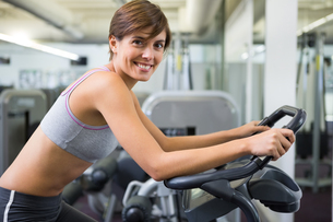 Fit brunette working out on the exercise bikeの写真素材 [FYI00002546]