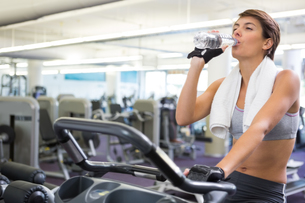 Fit woman taking a drink on the exercise bikeの写真素材 [FYI00002547]
