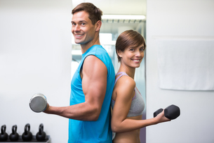 Fit couple lifting dumbbells together smiling at cameraの写真素材 [FYI00002548]
