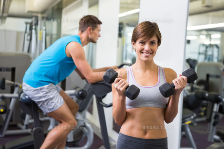 Fit brunette lifting weights smiling at cameraの写真素材 [FYI00002549]
