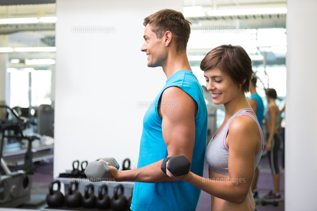 Fit happy couple lifting dumbbells togetherの写真素材 [FYI00002550]