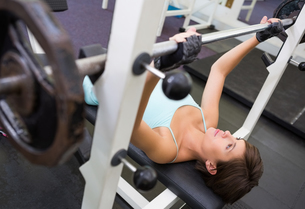 Fit brunette lifting heavy barbell lying on benchの写真素材 [FYI00002551]