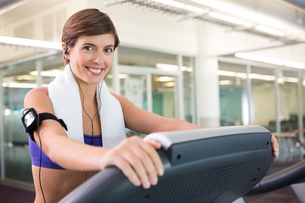 Fit brunette running on the treadmill listening to musicの写真素材 [FYI00002554]