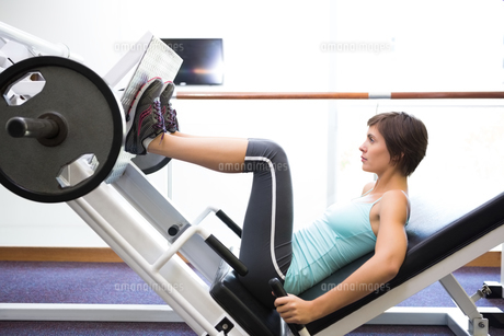 Fit brunette using weights machine for legsの写真素材 [FYI00002556]