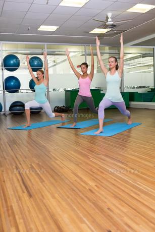 Yoga class in warrior pose in fitness studioの写真素材 [FYI00002561]