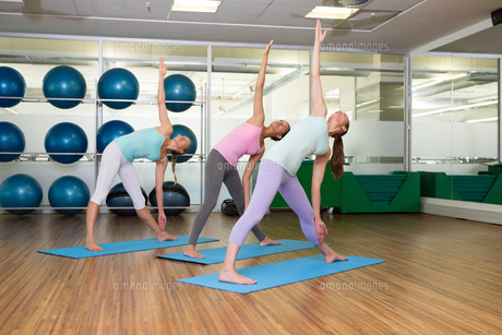 Yoga class in extended traingle position in fitness studioの写真素材 [FYI00002562]