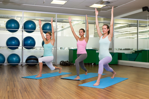 Yoga class in warrior pose in fitness studioの写真素材 [FYI00002563]
