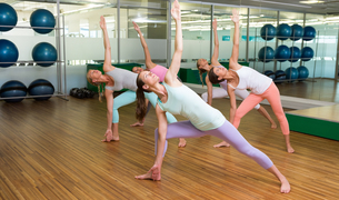 Yoga class in extended triangle pose in fitness studioの写真素材 [FYI00002566]