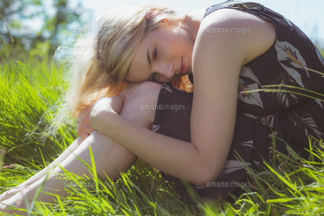 Pretty blonde in sundress sitting on grassの写真素材 [FYI00002567]